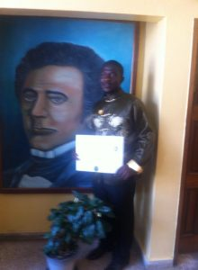 A proud recipient of the J. J.  Roberts scholarship poses with the president potrait